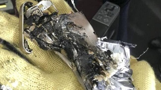 Remnants of a mobile phone that caught fire after it became crushed in a seat on board an aircraft